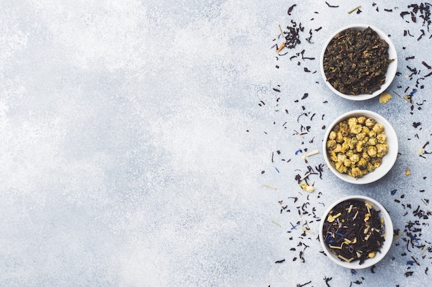 Różnorodność suchych liści herbaty i kwiatów w misce na szarym tle.