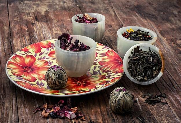 Różnorodność suchych liści herbaty w stosy jade na drewniane tła