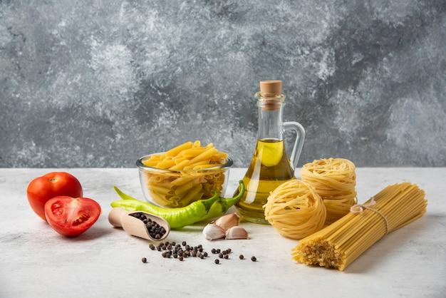 Różnorodność surowego makaronu, butelki oliwy z oliwek, ziaren pieprzu i warzyw na białym stole.