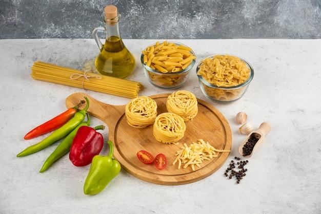Różnorodność surowego makaronu, oleju i świeżych warzyw na białym stole.