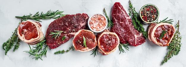 Różnorodność surowych steków z czarnego angusa prime mięsnych steków wołowych, polędwicy z polędwicy mignon lub grilla z przyprawami na jasnym tle. baner, widok z góry na przepis menu.