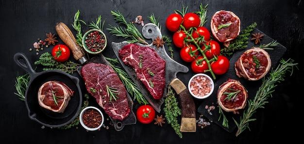 Różnorodność surowych steków z czarnego angusa prime stek wołowy rumsztyk, polędwica z polędwicy mignon lub grillowanie z przyprawami na czarnym tle. baner, widok z góry na przepis menu.