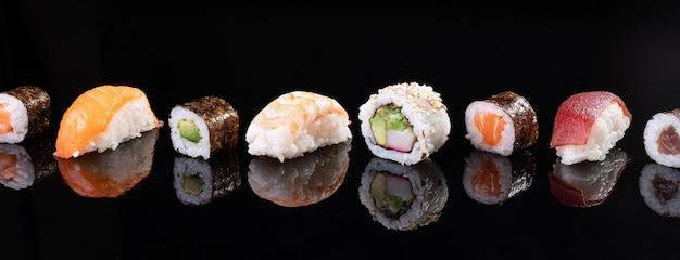 Różnorodność sushi na białym tle na czarnym tle. tradycyjne japońskie jedzenie.