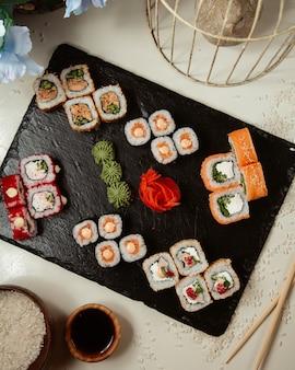 Różnorodność sushi rolki na czarnej desce.