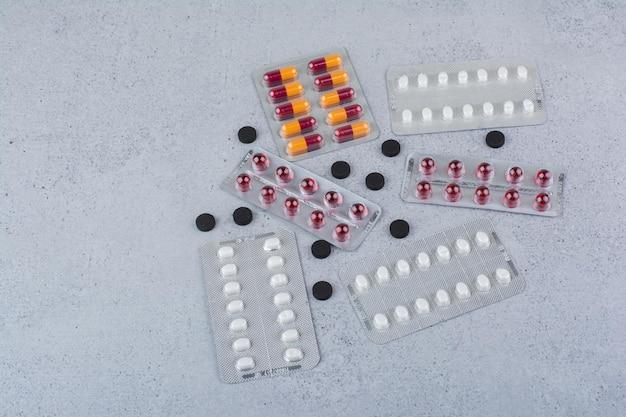 Różnorodność tabletek i kapsułek na marmurowej powierzchni. zdjęcie wysokiej jakości