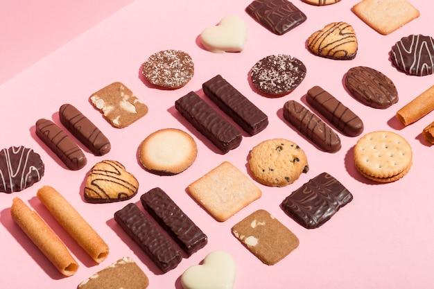 Różnorodność tradycyjnych ciasteczek ułożonych geometrycznie na różowym tle