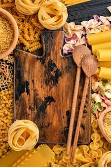 Różnorodność tradycyjnych włoskich makaronów: kolorowe spaghetti, tagliatelle, farfalle, penne, ptititm, noodle, fusilli, cannelloni na starym drewnianym tle. widok z góry z miejsca na kopię.