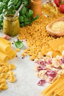 Różnorodność tradycyjnych włoskich makaronów: kolorowe spaghetti, tagliatelle, farfalle, penne, ptititm, noodle, fusilli, cannelloni
