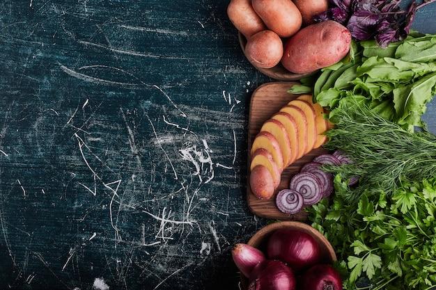Różnorodność warzyw na niebieskim stole z ziołami wokół.