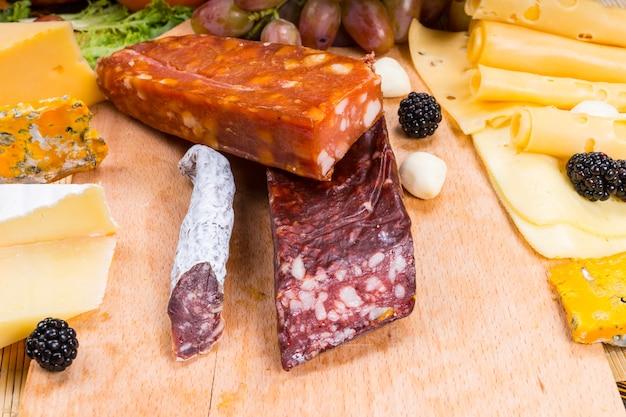 Różnorodność wędzonych i wędzonych mięs gourmet na drewnianej deski z serami i świeżymi owocami - apetyczne jedzenie dla smakoszy martwa natura