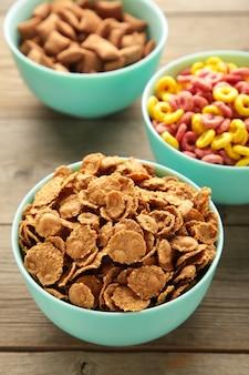 Różnorodność zbóż w miskach niebieskich, szybkie śniadanie na szarym tle drewnianych. zdjęcie pionowe