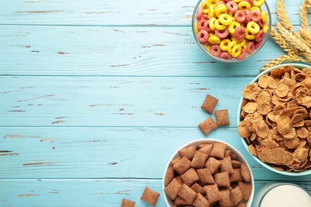 Różnorodność zbóż w niebieskich miskach, szybkie śniadanie na niebieskim tle drewnianych. zdjęcie pionowe