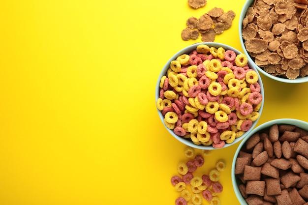 Różnorodność zbóż w niebieskich miskach, szybkie śniadanie na żółtym tle. zdjęcie pionowe