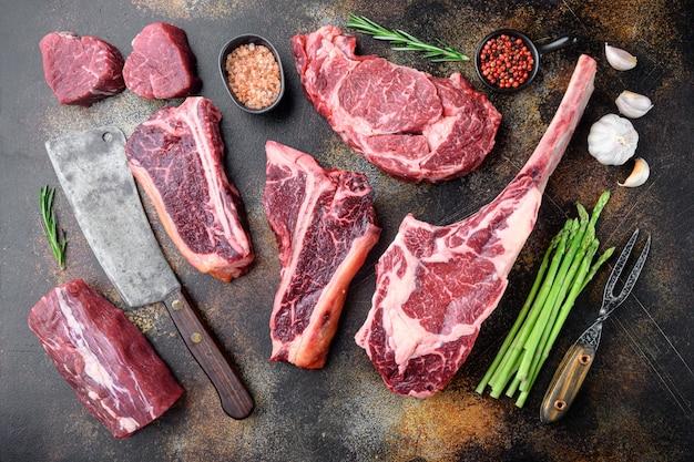 Różnorodność zestawu steków mięsnych raw black angus prime, tomahawk, kości t, stek klubowy, żeberka i kawałki polędwicy, na starym ciemnym rustykalnym stole, widok z góry na płasko