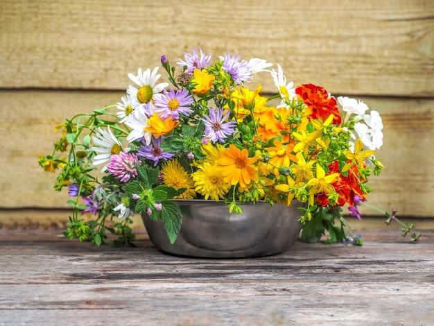 Różnorodny bukiet letnich polnych kwiatów w zbliżeniu metalowej filiżanki