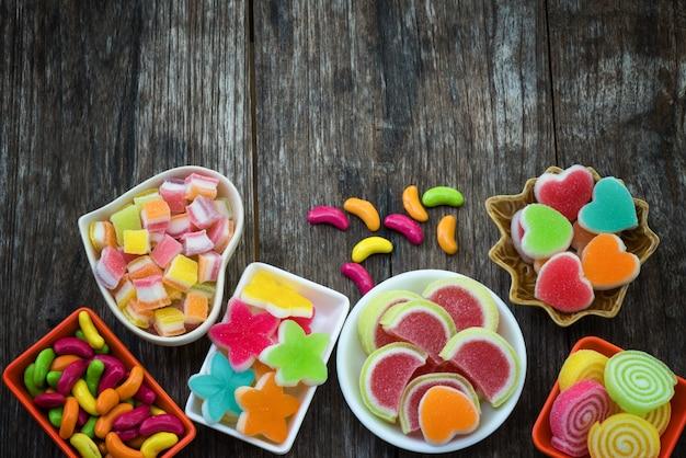 Różnorodny kolorowy cukierkowy cukierek w zbiorniku na starej drewnianej desce