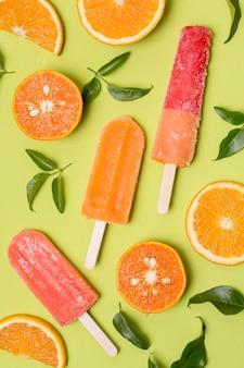 Różnorodny smak lodów na patyku z kawałkami pomarańczy