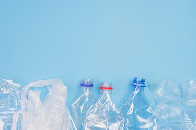 Różny plastikowy śmieci na błękitnym tle.