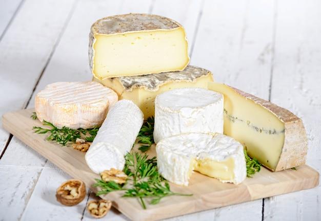 Różny ser z orzechami włoskimi na białej drewnianej desce