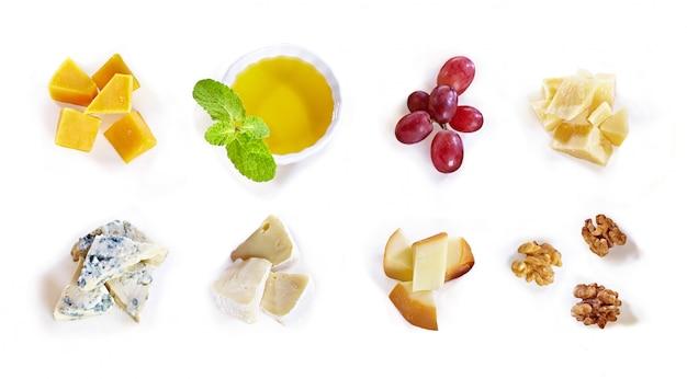 Różny typ ser z miodem, winogronem, dokrętkami na białym tle. widok z góry. plasterki sera pleśniowego, cheddaru, parmezanu, maasdamu i brie