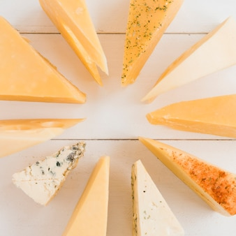 Różny typ trójkątny ser układający w kółku na białym biurku