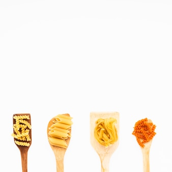Różny włoski surowy makaron na drewnianej szpachelce nad odosobnionym tłem