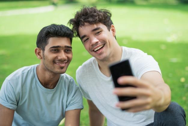 Rozochoceni beztroscy młodzi człowiecy bierze selfie na telefonie