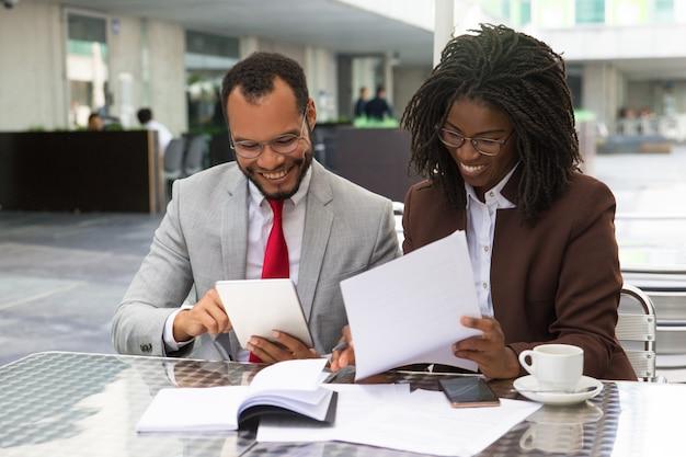 Rozochoceni biznesowi koledzy sprawdza dokumenty