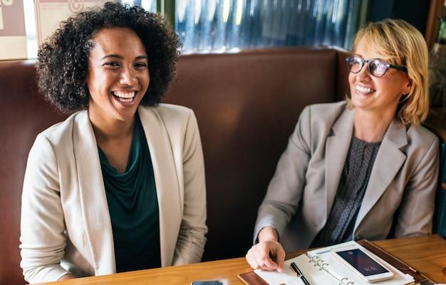 Rozochoceni bizneswomany relaksuje przy kawiarnią