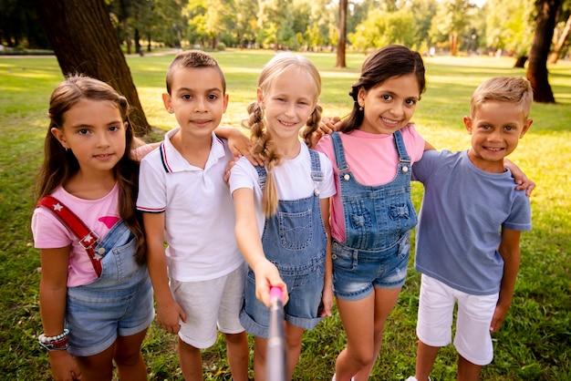 Rozochoceni dzieci bierze selfie w parku