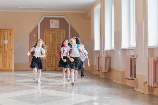 Rozochoceni dzieciaki biega w szkolnym korytarzu