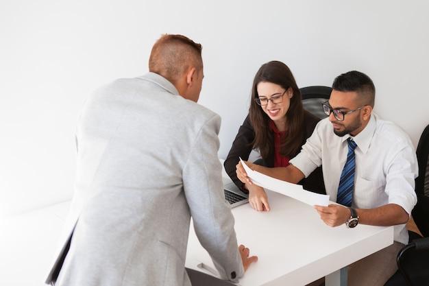 Rozochoceni finansiści egzaminuje biznesowych dokumenty
