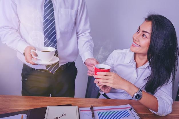 Rozochoceni koledzy dzieli kawę w biurze i cieszy się wpólnie.