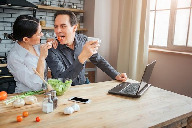 Rozochoceni ludzie siedzą razem w pokoju. kobieta karmić faceta z pomidorami. trzyma usta otwarte. mężczyzna trzymać biały kubek.