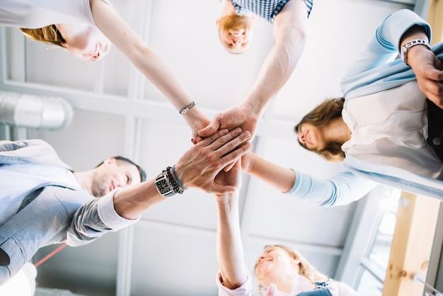 Rozochoceni ludzie trzyma ręki w biurze wpólnie