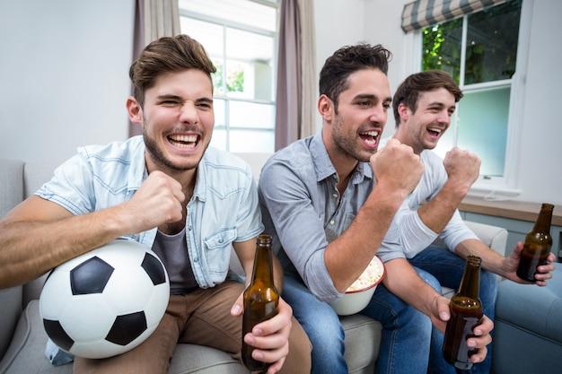 Rozochoceni męscy przyjaciele ogląda mecz piłkarskiego w tv