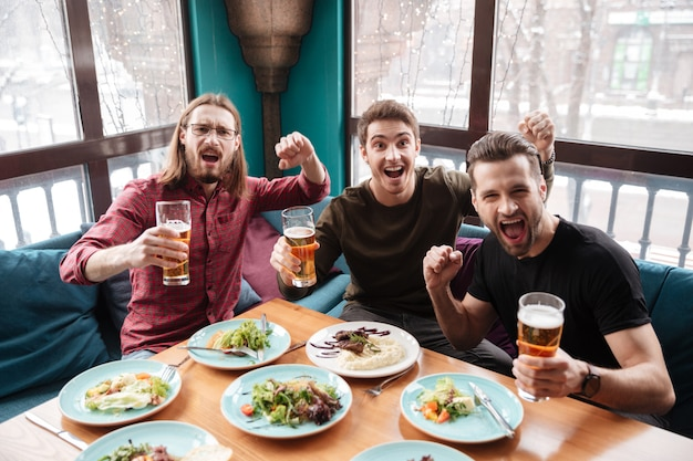 Rozochoceni mężczyzna przyjaciele siedzi w kawiarni podczas gdy pijący piwo.