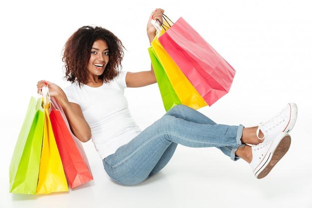 Rozochoceni młodzi afrykańscy kobiety mienia torba na zakupy.