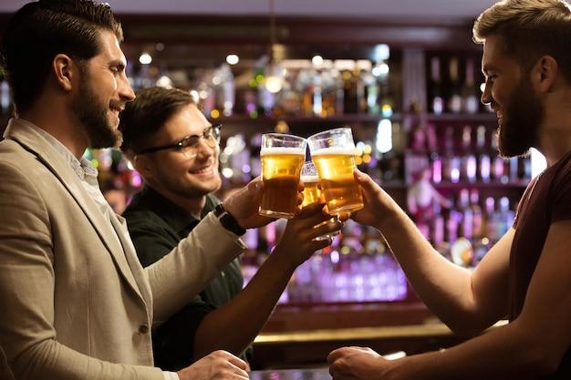 Rozochoceni młodzi człowiecy wznosi toast z piwem