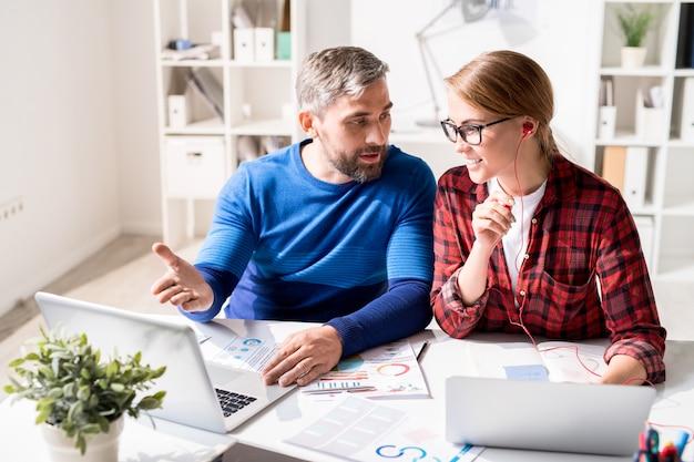 Rozochoceni młodzi koledzy dyskutuje marketingową analizę