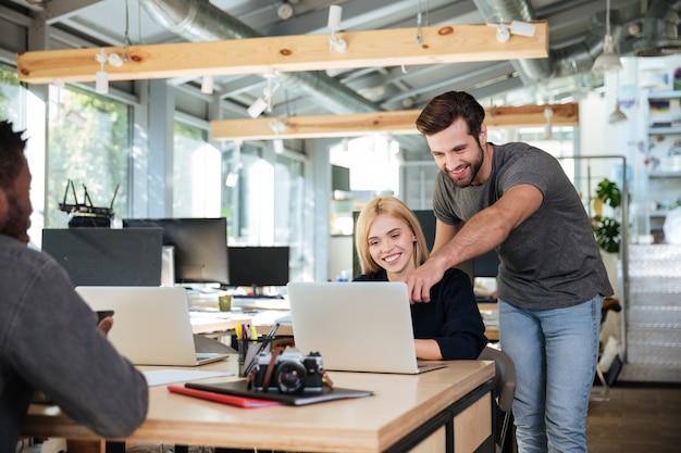Rozochoceni młodzi koledzy siedzi w biurowym coworking