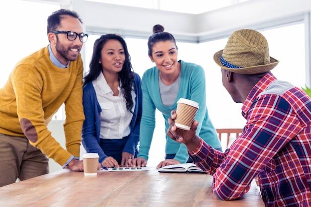 Rozochoceni młodzi ludzie biznesu dyskutuje z each inny przy kreatywnie biurem