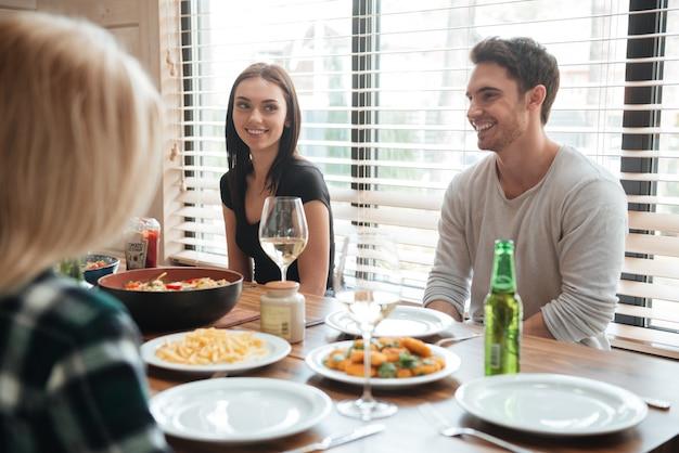 Rozochoceni młodzi ludzie cieszy się posiłek podczas gdy siedzący przy łomotanie stołem