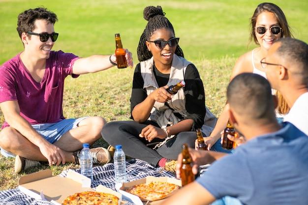 Rozochoceni młodzi ludzie rozwesela z piwnymi butelkami w parku. szczęśliwi przyjaciele siedzi na łące i pije piwo. koncepcja wypoczynku