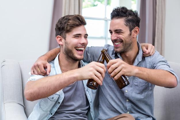 Rozochoceni młodzi męscy przyjaciele wznosi toast piwo w domu