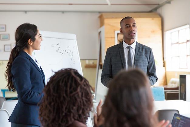 Rozochoceni młodzi mówcy stoi blisko whiteboard