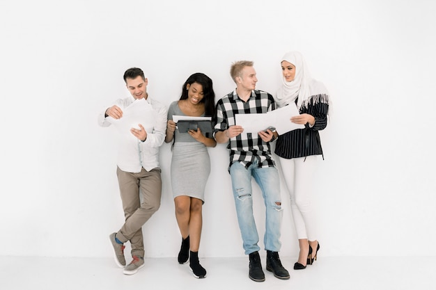 Rozochoceni multiracial fachowi ludzie biznesu lub ucznie uśmiecha się wpólnie i opowiada stojący na biel ściany tle