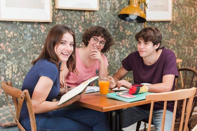 Rozochoceni nastolatkowie robi pracie domowej przy kawiarnia stołem