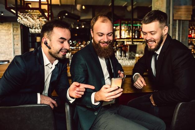 Rozochoceni pozytywni i mili młodzi biznesmeni siedzą w barze. patrzą na telefon. pierwszy facet na to wskazuje. uśmiechają się.