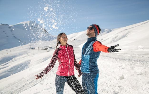 Rozochoceni przyjaciele bawić się z śniegiem w górze